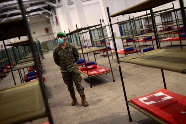 A soldier stands next to beds.