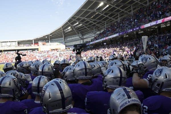 Football players wearing purple jerseys huddle