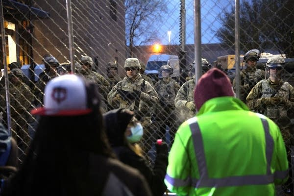 Protesters face off against police behind a fence.