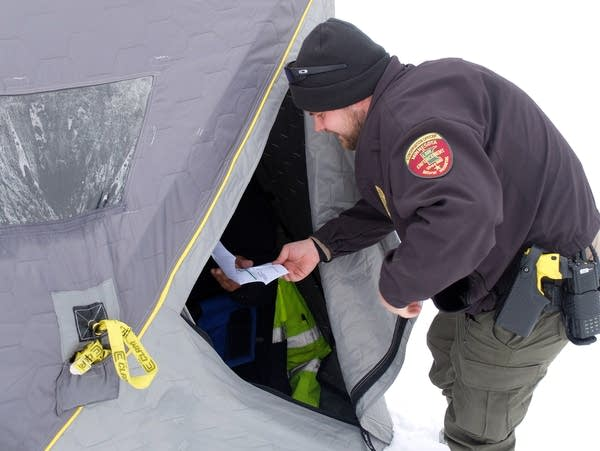 a conservation officer holds a piece of paper