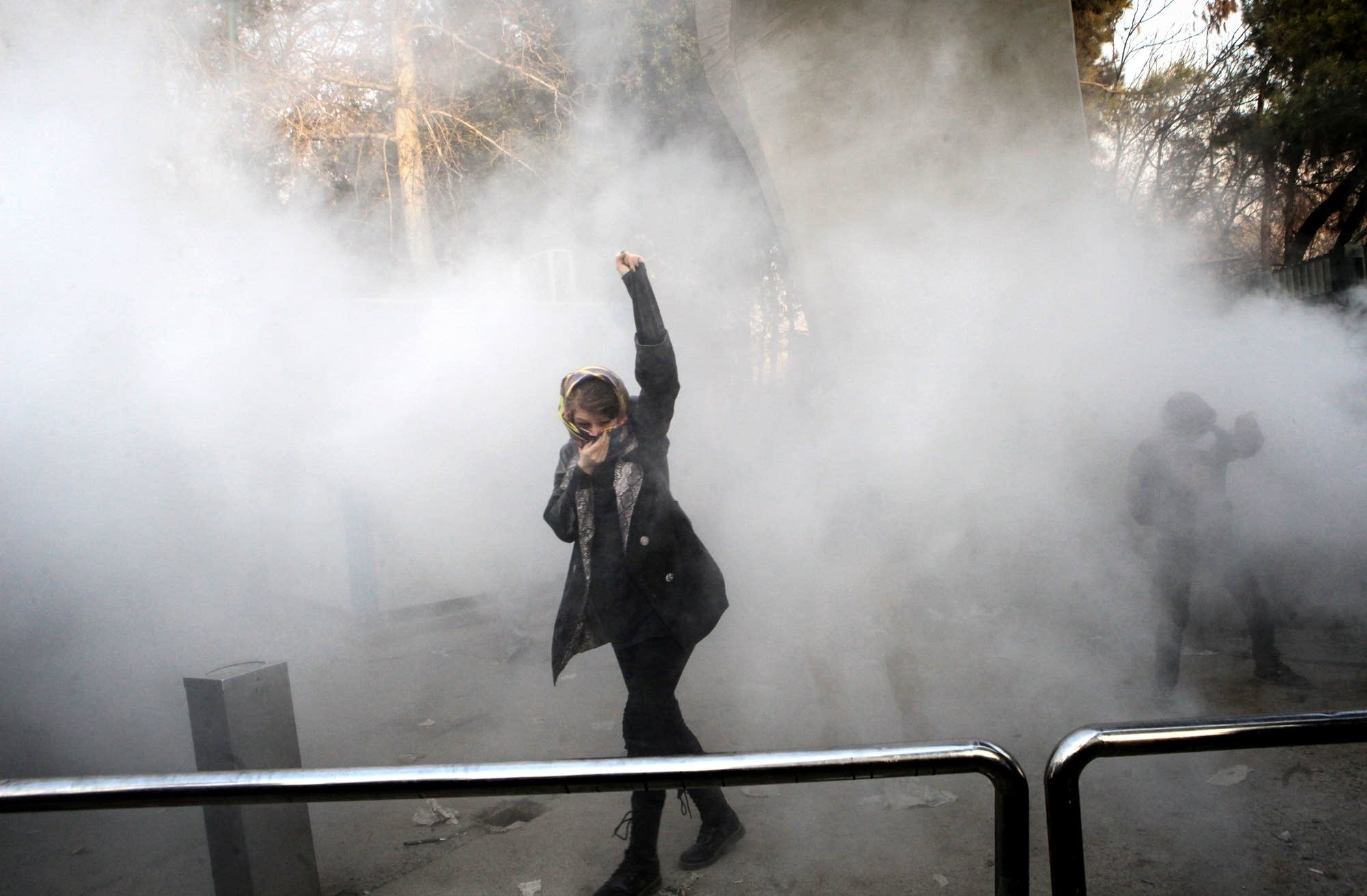 An Iranian woman raises her fist amid the smoke of tear gas.