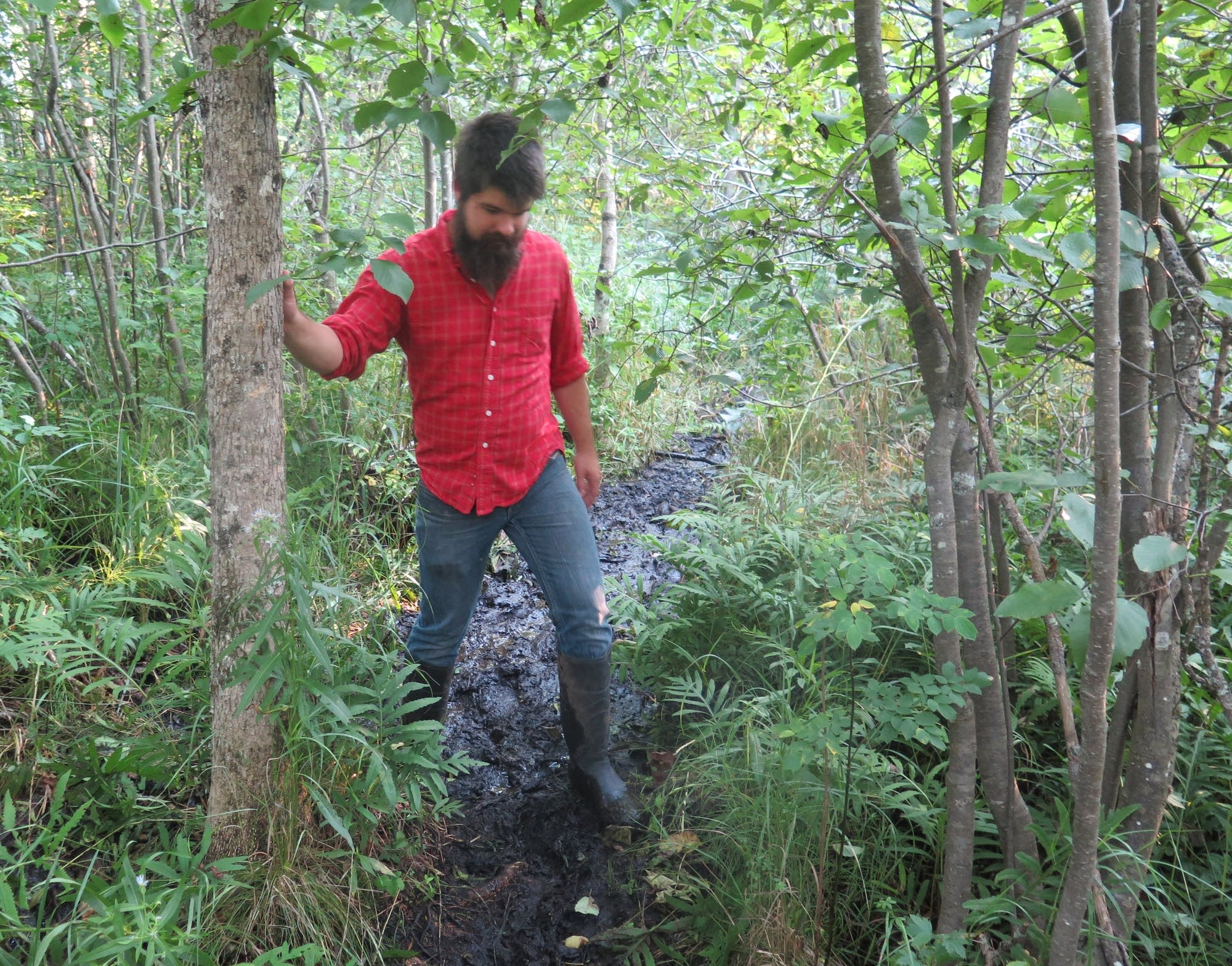 Blake Romenesko navigates a muddy trail to his campsite.