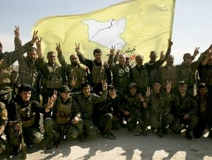 U.S.-backed Syrian Democratic Forces (SDF) fighters pose for a photo