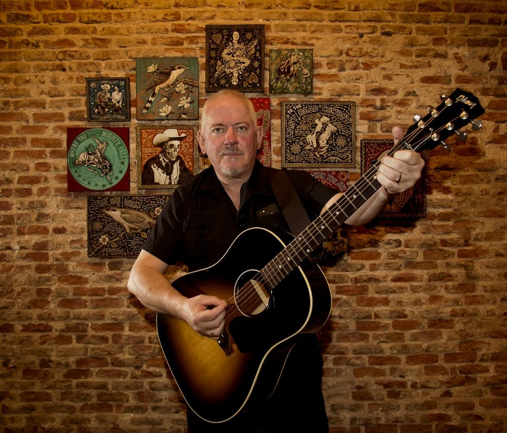 Jon Langford poses with a guitar in front of some of his original visual art.
