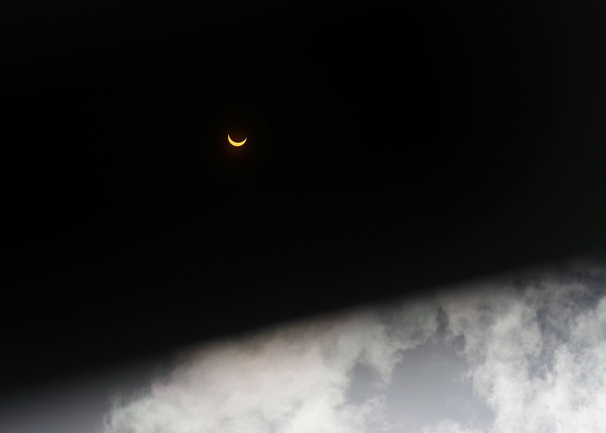 The solar eclipse viewed through dark eclipse glasses in Miami.