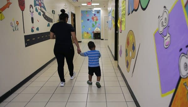 A young migrant boy walks with a Comprehensive Health Services caregiver.