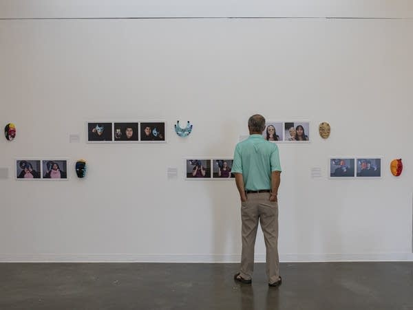 Man looking at white wall with hanging masks and photos.