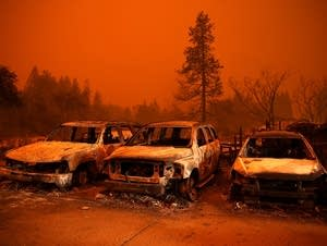 Cars destroyed by the Camp Fire sit in the lot at a used car dealership