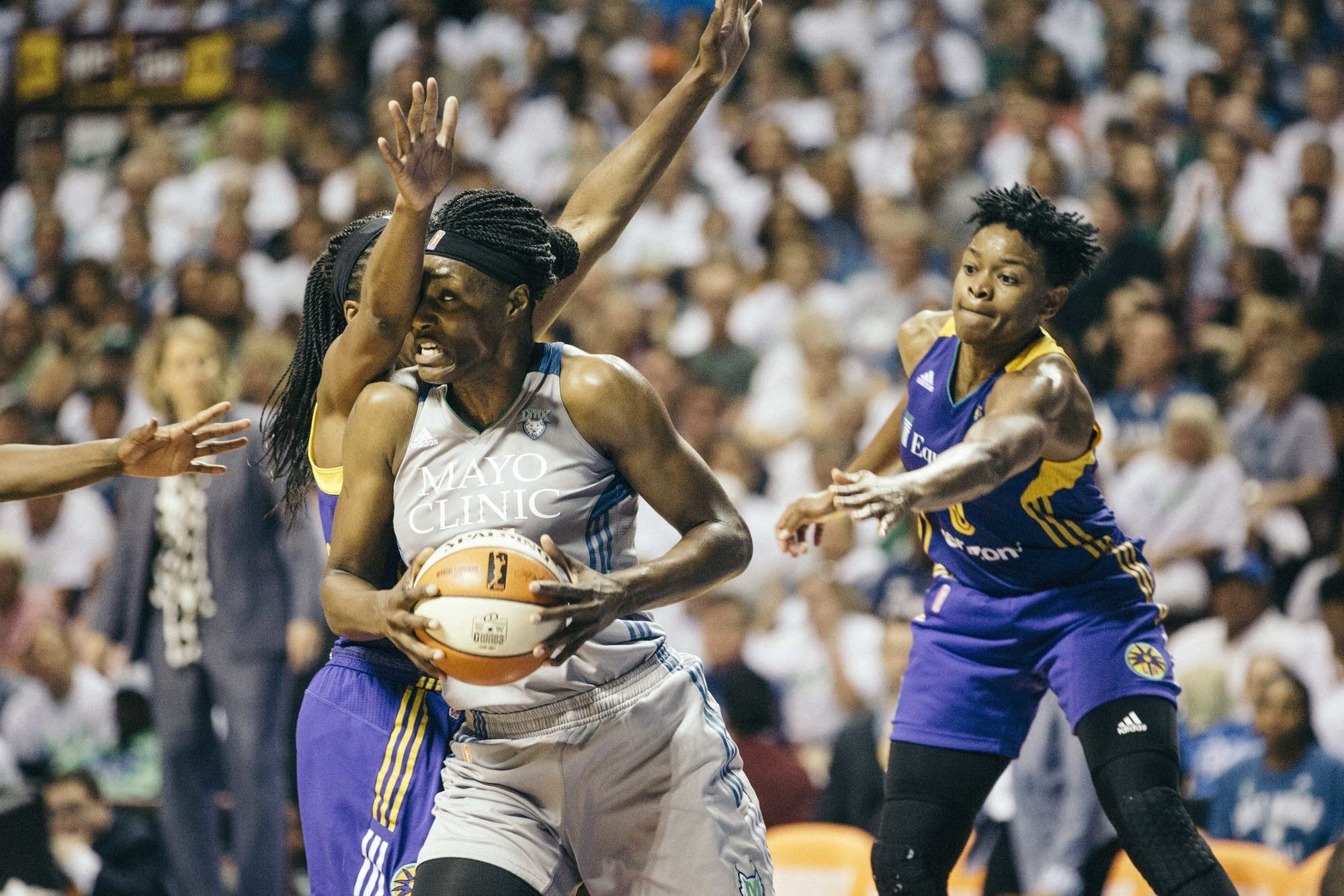 Lynx center Sylvia Fowles posts up against two LA Sparks defenders.