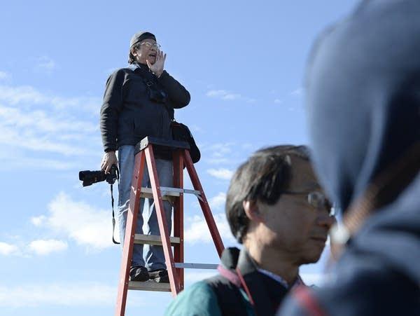 A photographer on a ladder arranges a photo shoot