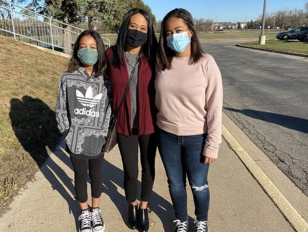 Three people wear masks while waiting in line to vote