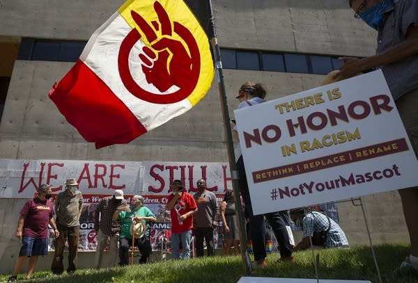People stand beneath an American Indian Movement flag.