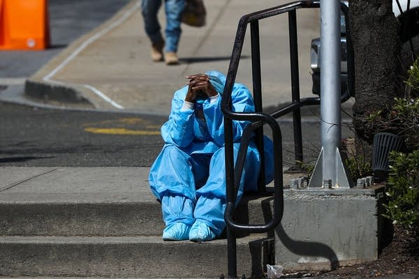 A fatigued health care worker takes a moment outside a hospital.