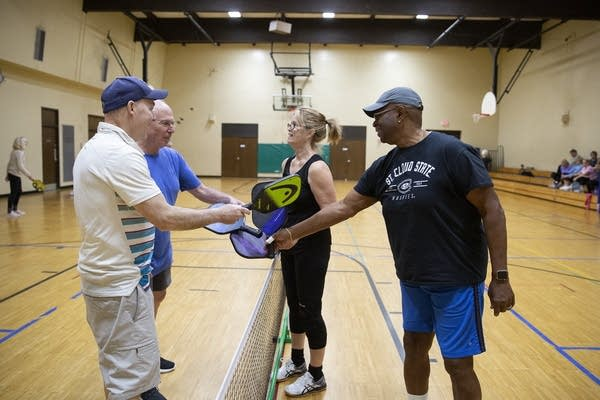 Four people standing over a net touch paddles inside a gym.
