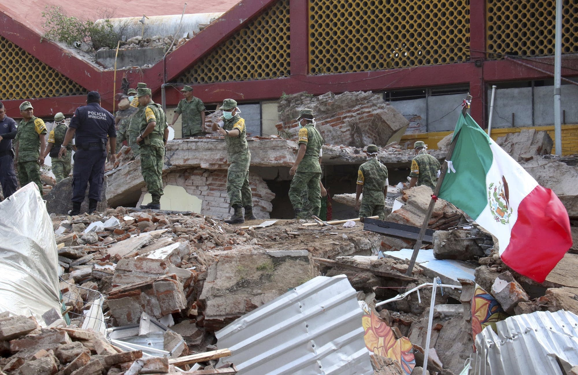 Soldiers remove debris from a partly collapsed municipal building
