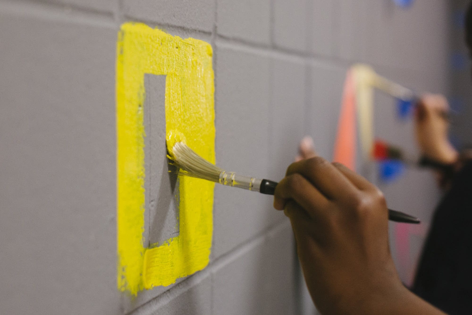 A student paints a square on the mural.