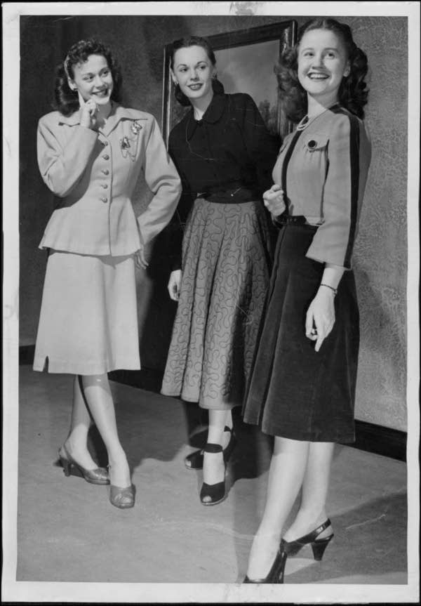Women standing and smiling during a fashion show.