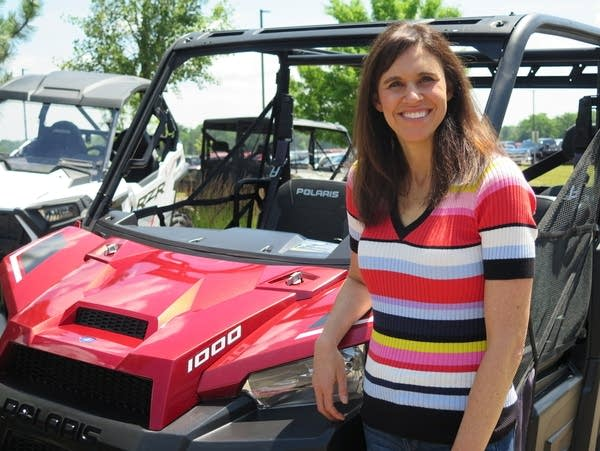 A woman stands next to an all terrain vehicle