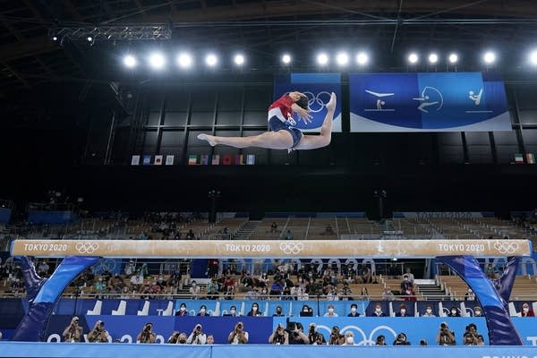 A woman leaps on beam.