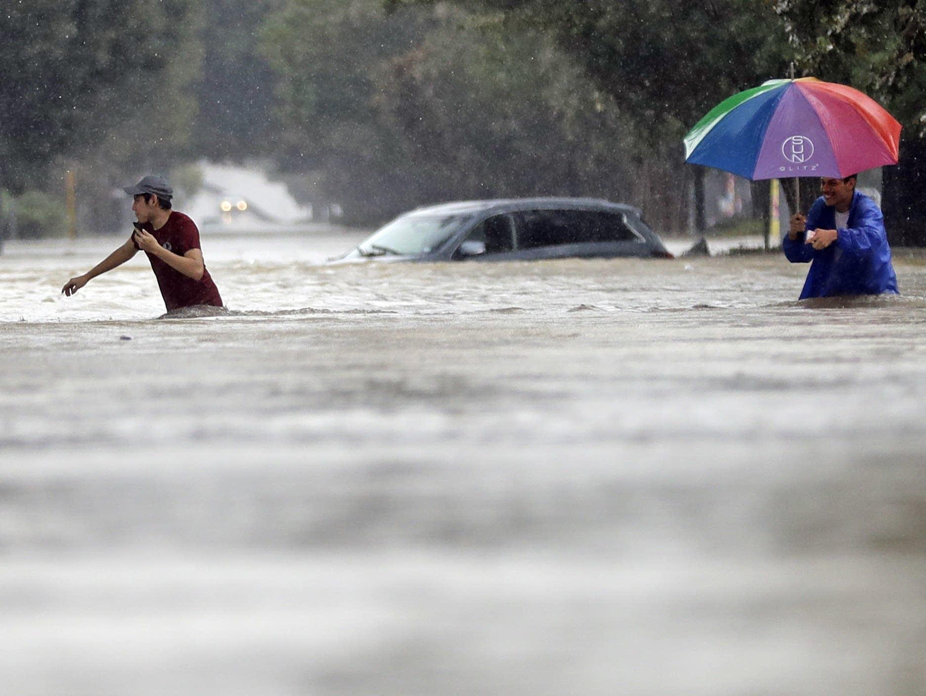 Moses Juarez Anselmo Padilla wade through floodwaters