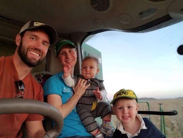 A family poses on a farm machine