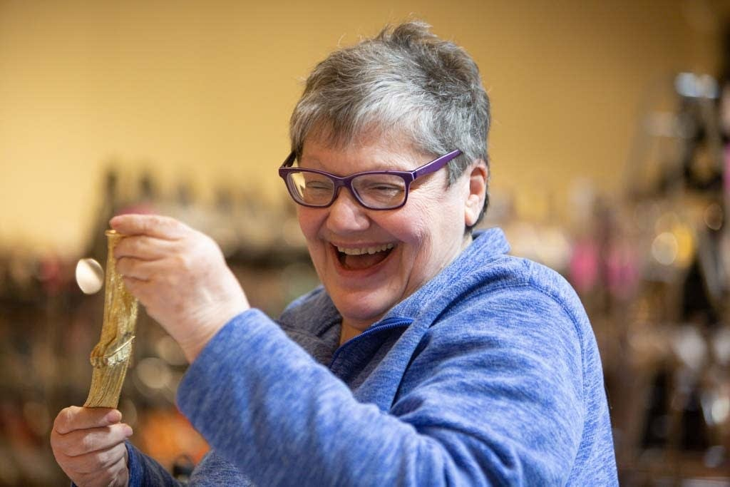 Pam Philipp, known as the head fairy godmother, sorts jewelry.