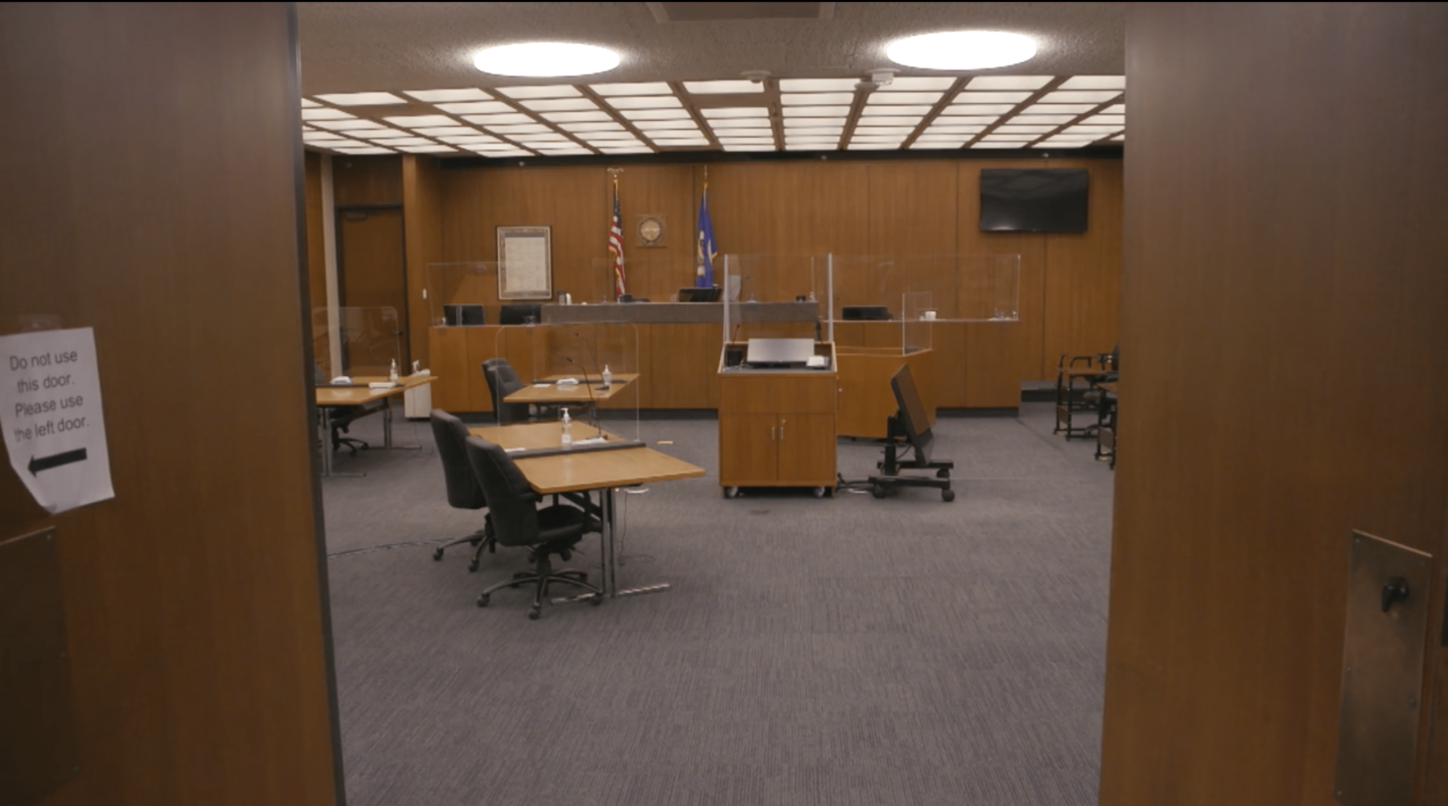 The inside of a courtroom with plastic barriers.