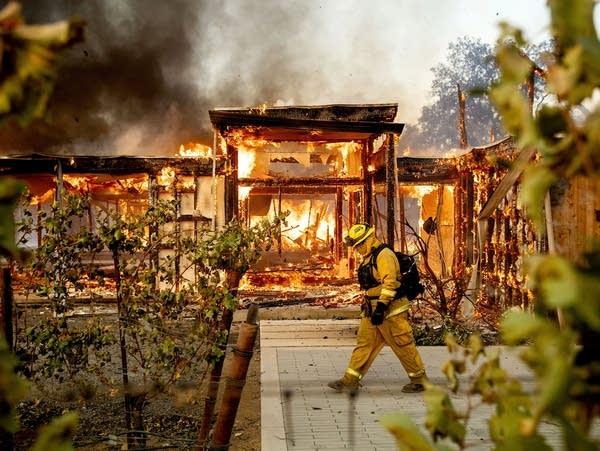 Woodbridge firefighter Joe Zurilgen passes a burning home