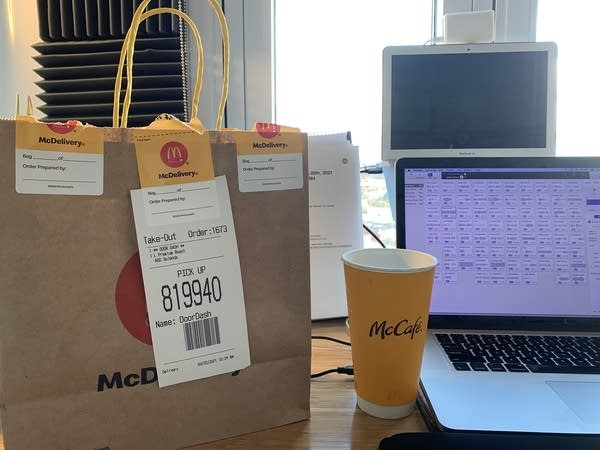 "A McDonalds delivery bag next to a ""McCafe"" coffee cup and a laptop"