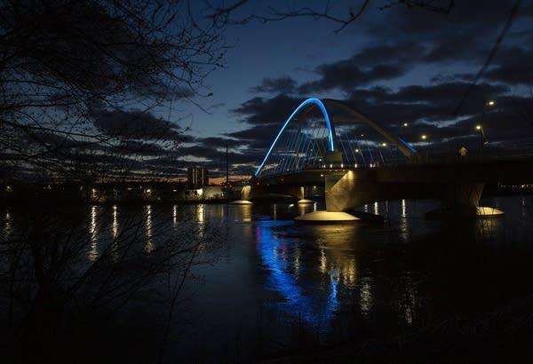 A bridge is lit blue at dusk.