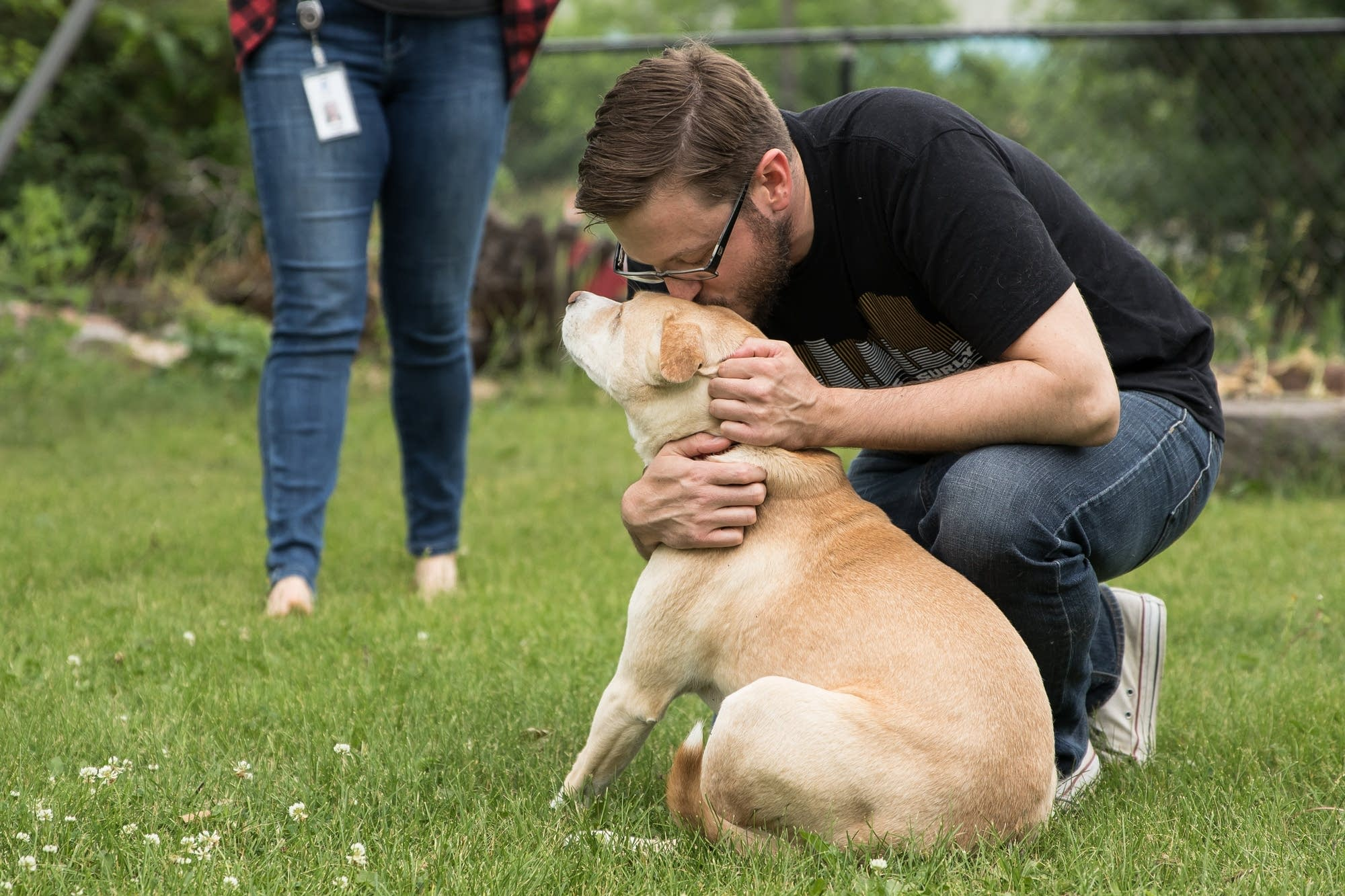Mike Liay kisses his dog Archie's head in his backyard.