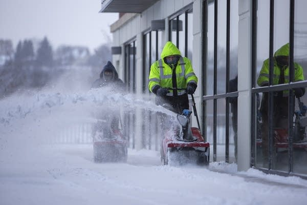 Herlbelto Rosendo (right) and Jose Suarez snowblows sidewalks.