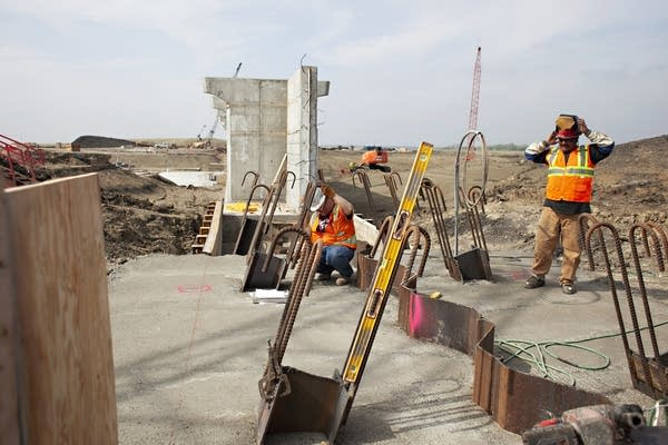 Two construction workers work on a structure.