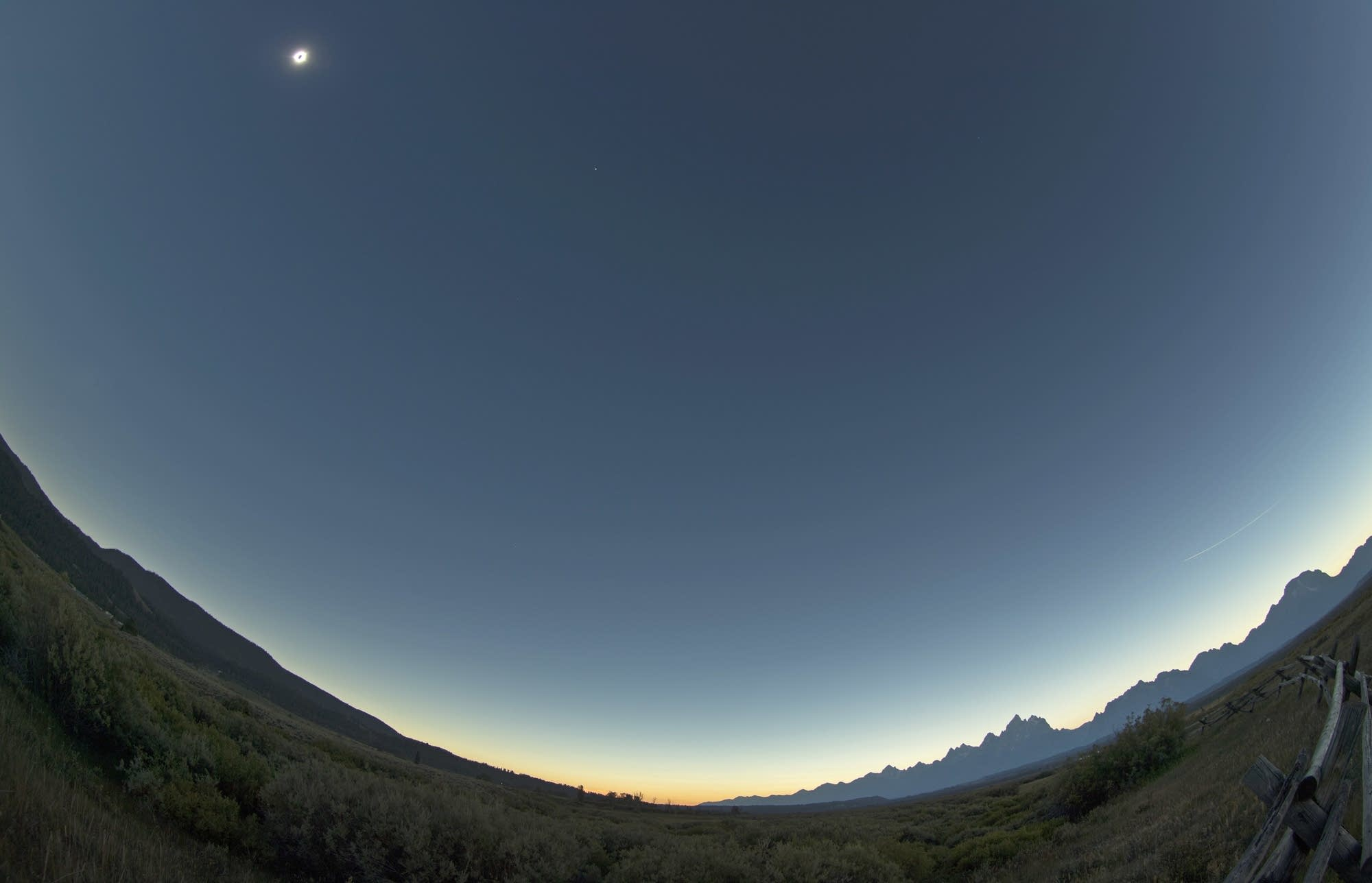 The sun is in full eclipse over Grand Teton National Park.
