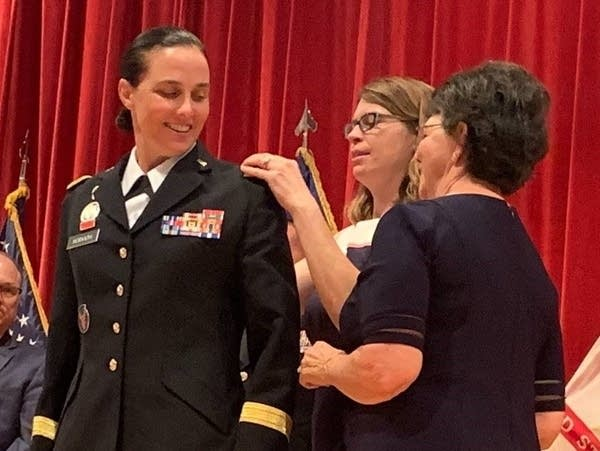 Stefanie Horvath's wife and her mother pin the insignia of her new rank.