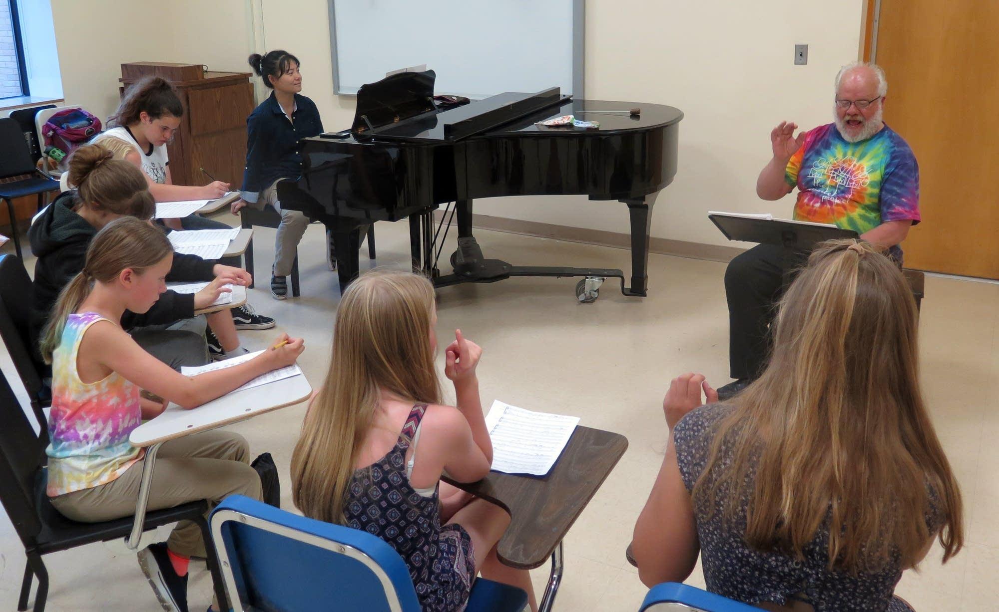 Director Warren Friesen, composer Wang Jie rehearse children's chorus.