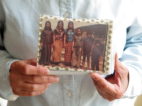 Sova Niev holds a photo of her and her siblings in a refugee camp.