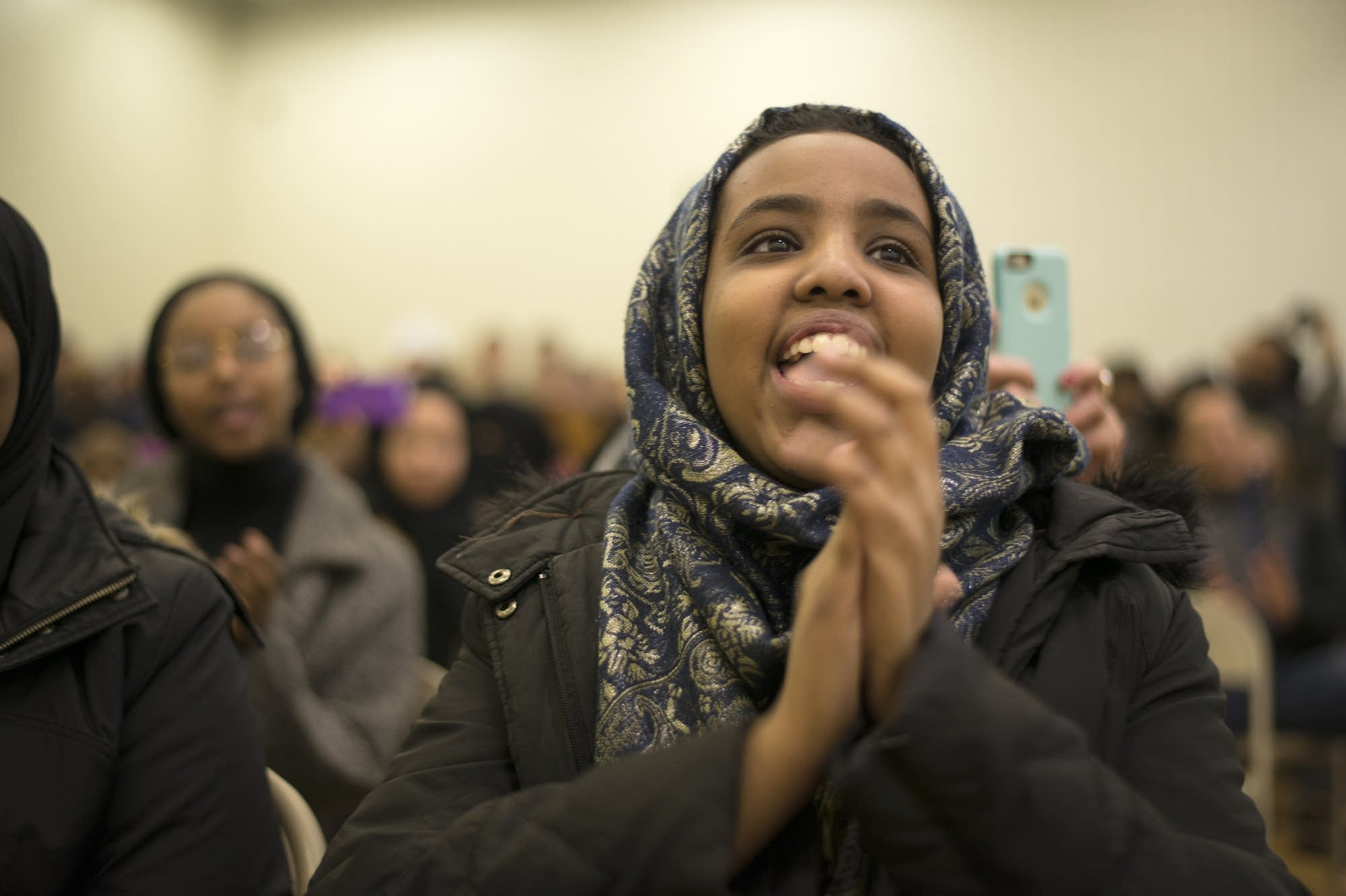Ikran Issa cheers as Rep. Ilhan Omar speaks to a packed house.