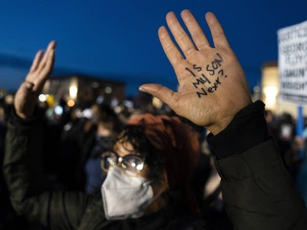 A demonstrator raises their hands
