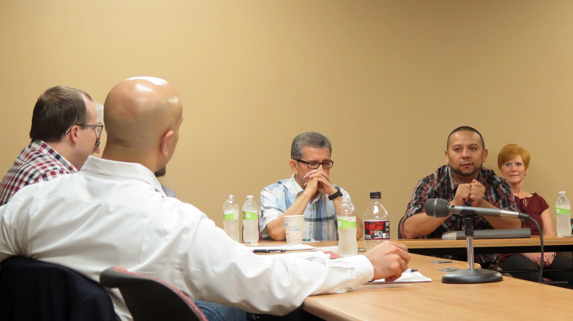 Neel Kashkari listens to an immigrant business owner in Worthington.