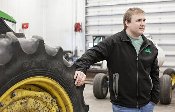 A man leans against the wheel of a tractor.