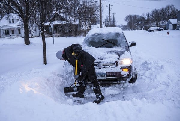 Adam Fischer shovels out his vehicle to go to work.