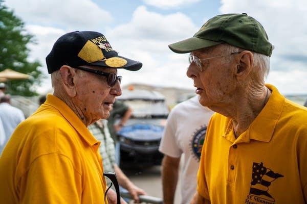 World War II veterans Andy Anderson, left, and Ken Schutt greet each other.