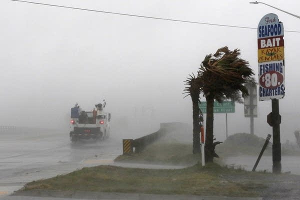 A work truck drives on Highway 24 as wind from Florence blows palm trees.