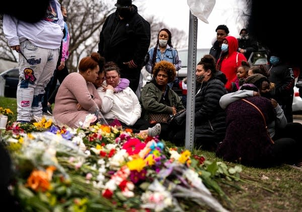 People sit at a memorial site surrounded by flowers.