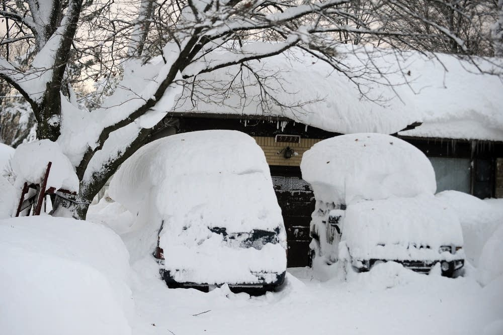 Cars with snow atop the roofs.