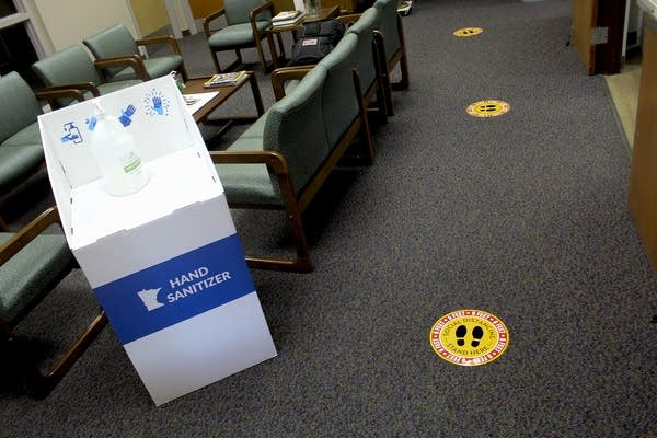 A bottle of hand sanitizer sits on top of a box near floor stickers.