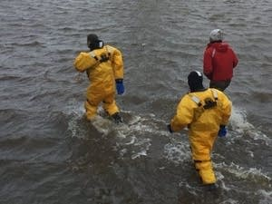 U.S. Army Corps of Engineers crew walks through Lake Superior floodwaters.