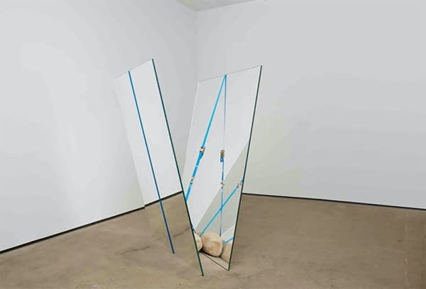 """Art installation: 2 mirrors strapped in """"V"""" shape with rock at bottom of V"""