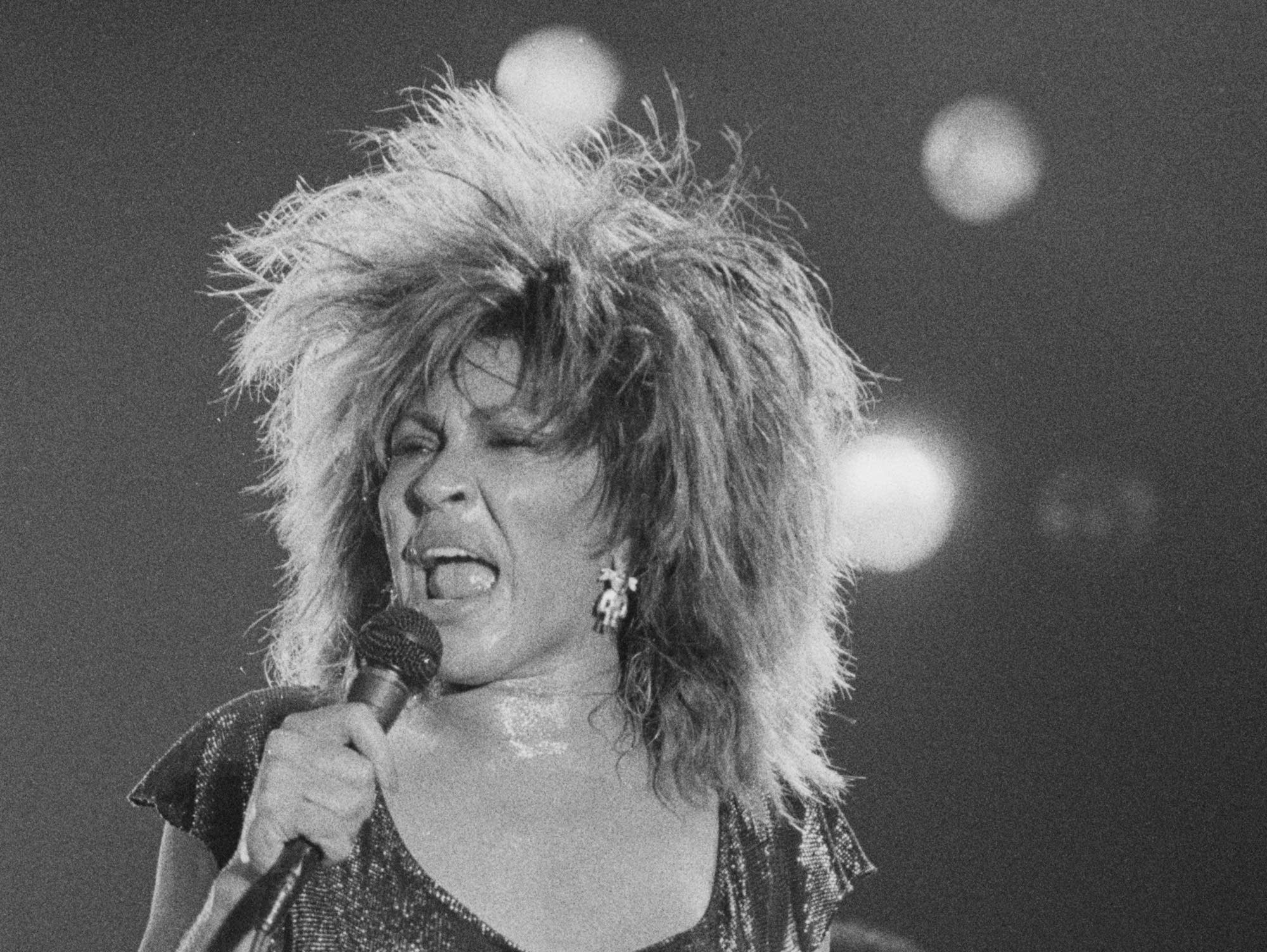 Tina Turner sings into microphone.